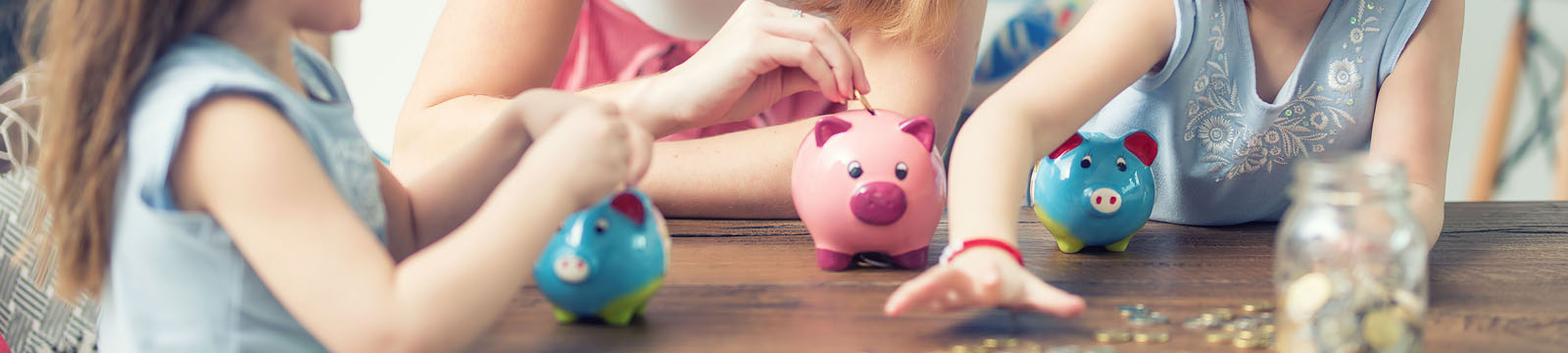 woman and two children's hands putting coins into piggy bank