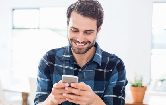 man looking at mobile phone while smiling