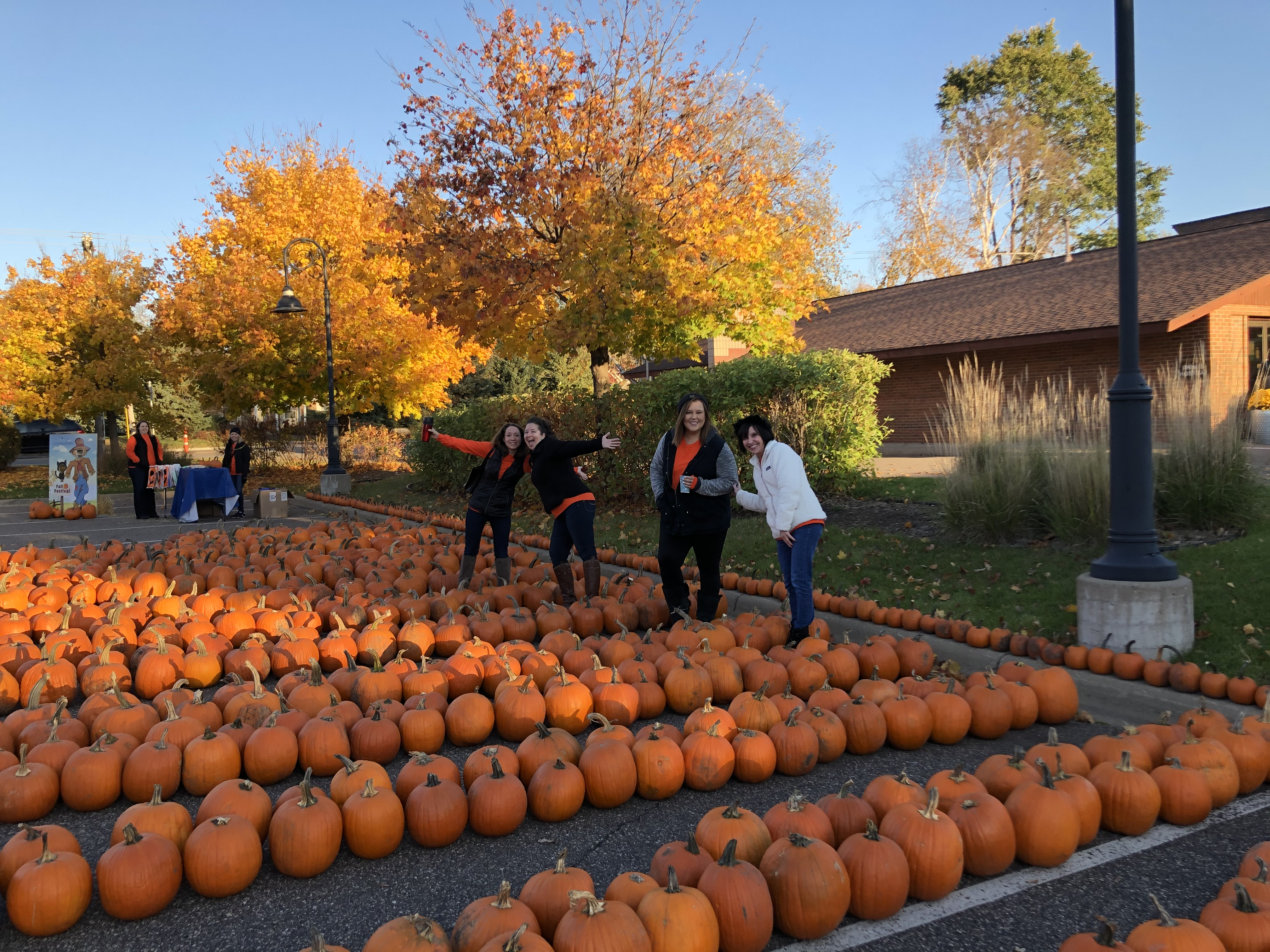 Gateway Bank associates standing around pumpkins at the fall festival laughing.